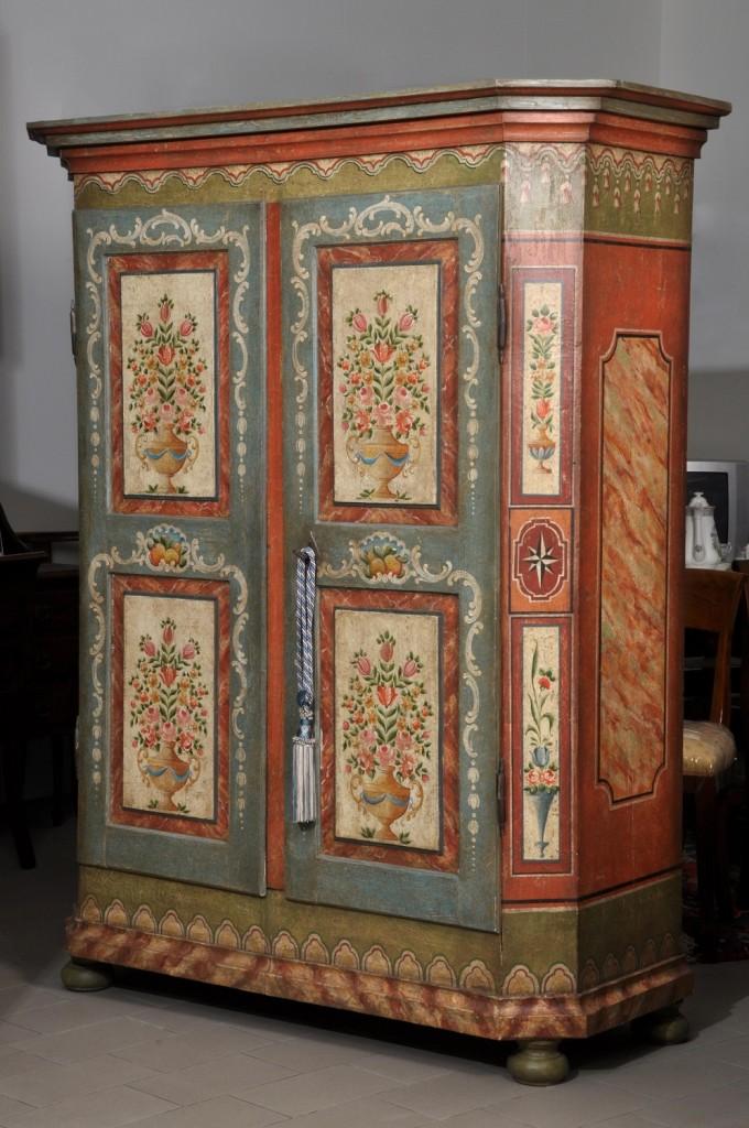 armadio scantonato a 2 ante riprodotto in stile tirolese con importanti decorazioni fatte a mano e ricche pitture