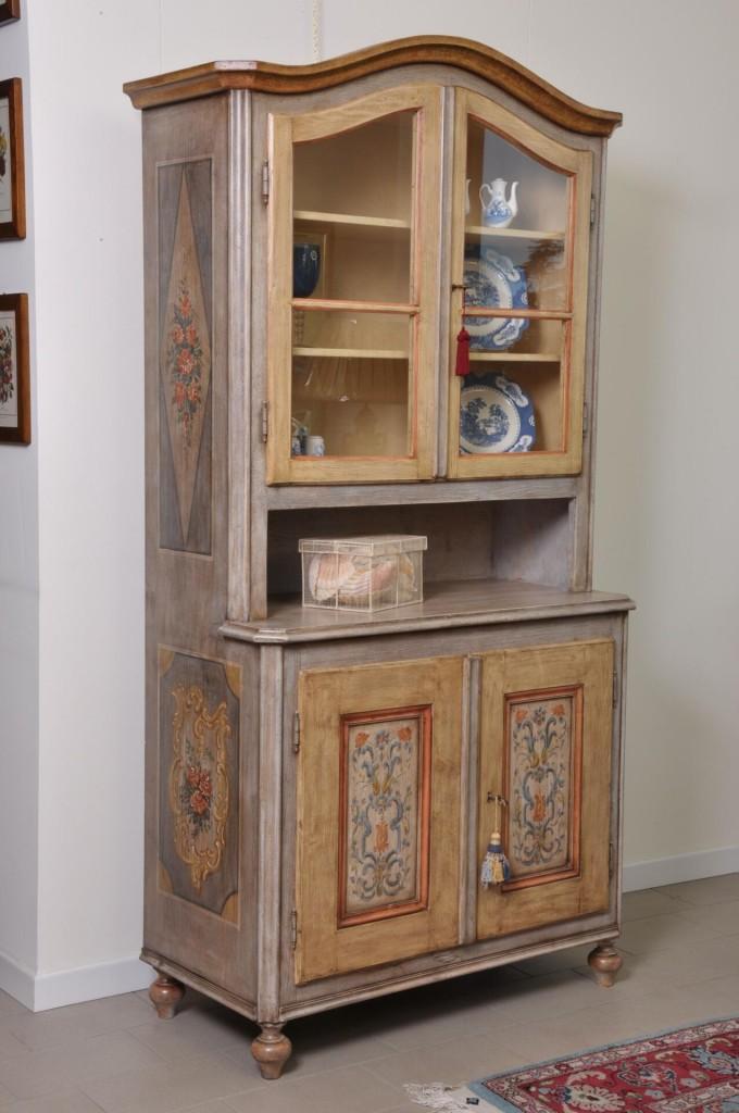 vetrina credenza sagomata e decorata a mano in stile tirolese prodotta e dipinta artigianalmente su misura arredo di lusso per prestigiose case di montagna e importanti residenze montane