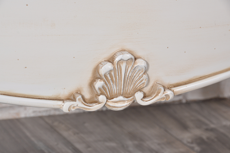 importante intaglio a forma di conchiglia realizzato a mano su essenza di tiglio massello richiama la tipicità degli arredi in stile francese